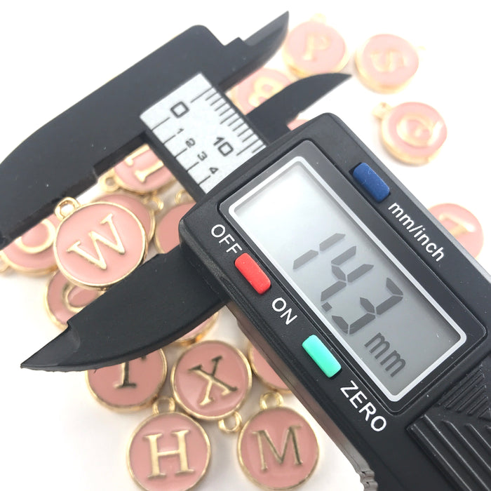 Pink and gold round letter charms, on a digital ruler that reads 14.3mm