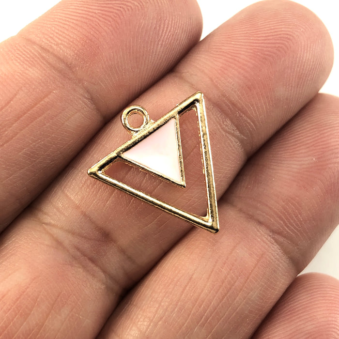 pink and gold triangle shaped jewerly charms, sitting on a hand to show scale