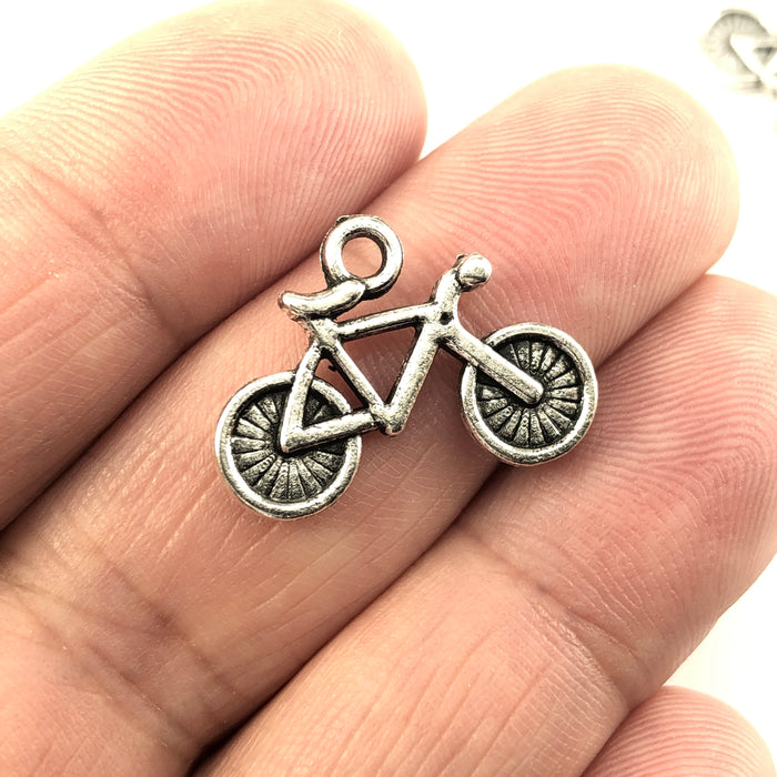 bicycle shaped jewerly charms in an antique silver finish, sitting on a hand to show scale