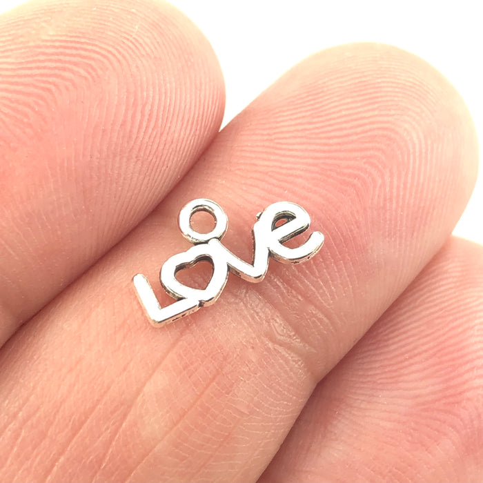 silver colour charm that in the shape of the word love, sitting on a hand to show scale