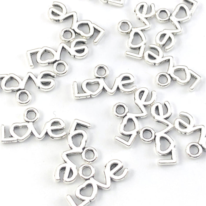 pile of silver colour charm that in the shape of the word love