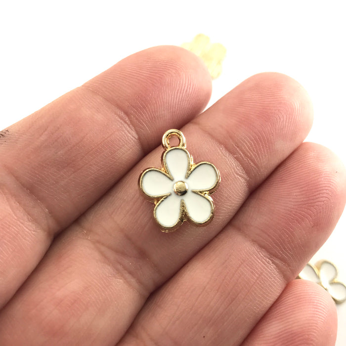 white and gold flower shaped jewelry charms, on a hand to show scale