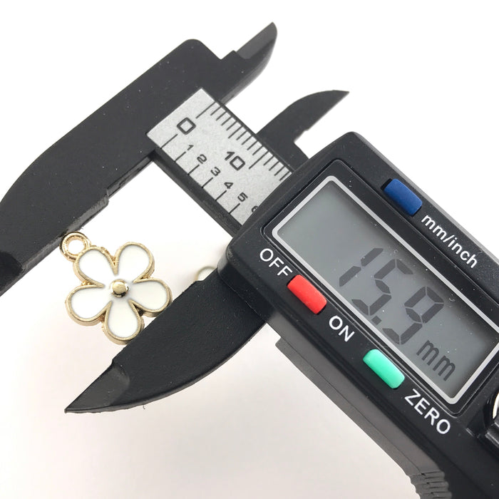 white and gold flower shaped jewelry charms, on a digital ruler that reads 15.9mm