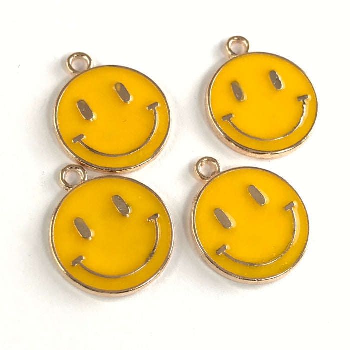 yellow and gold round flat jewerly charms that have a smiley face on them