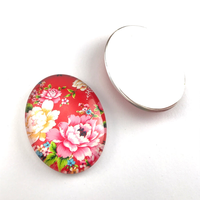 front and back of oval glass cabochon with flower design