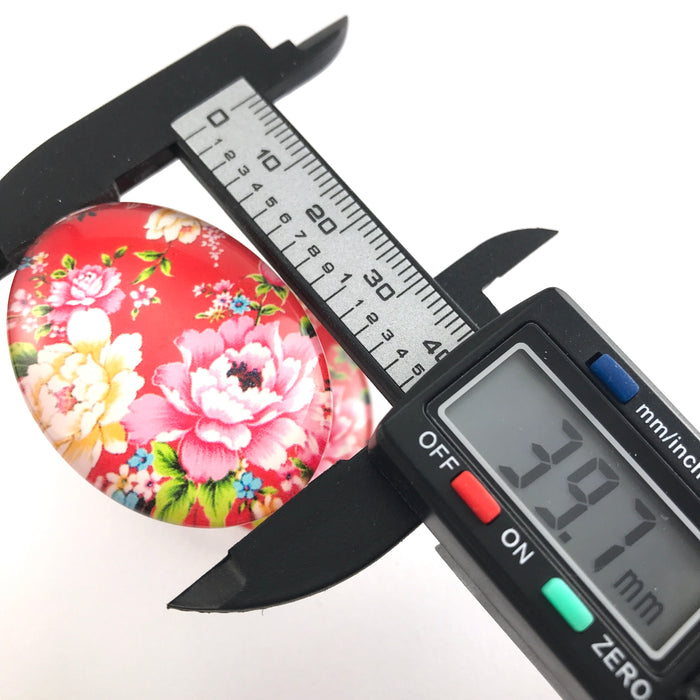 oval glass cabochon with flower design, on an electronic ruler that reads 39.7mm