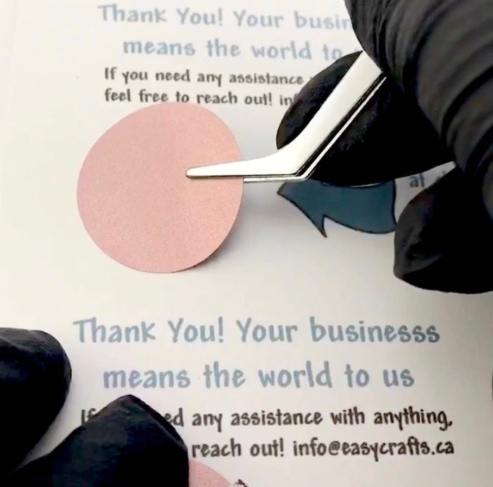 a hand placing a rose gold round sticker onto paper using tweezers