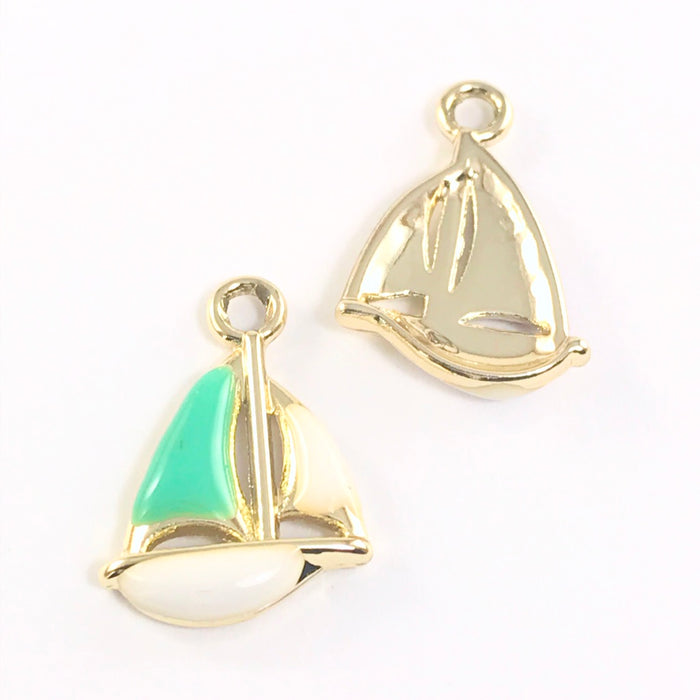 front and back of a jewelry charm that looks like a sailboat