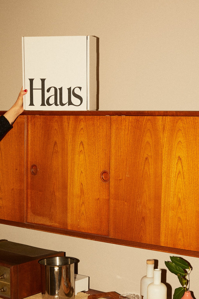 A hand reaches for a box of Haus on a shelf.
