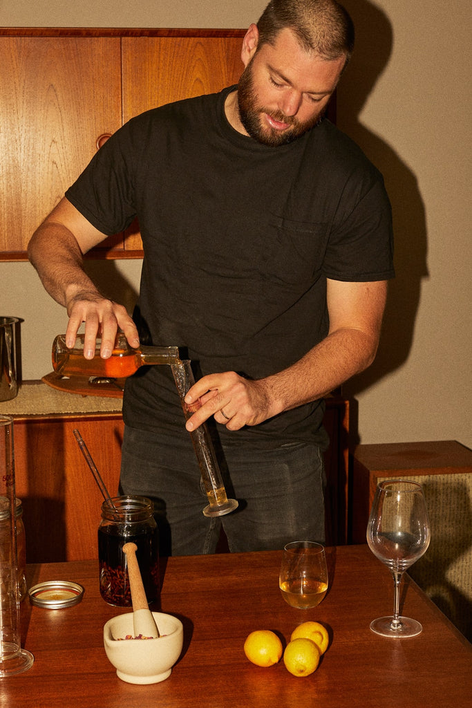 Woody Hambrecht mixes and makes aperitifs on a wooden table.