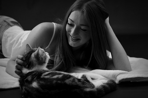 girl with her cat on a bed