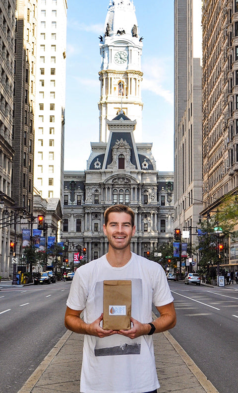 Blaise holding a bag of coffee beans in Philadelphia