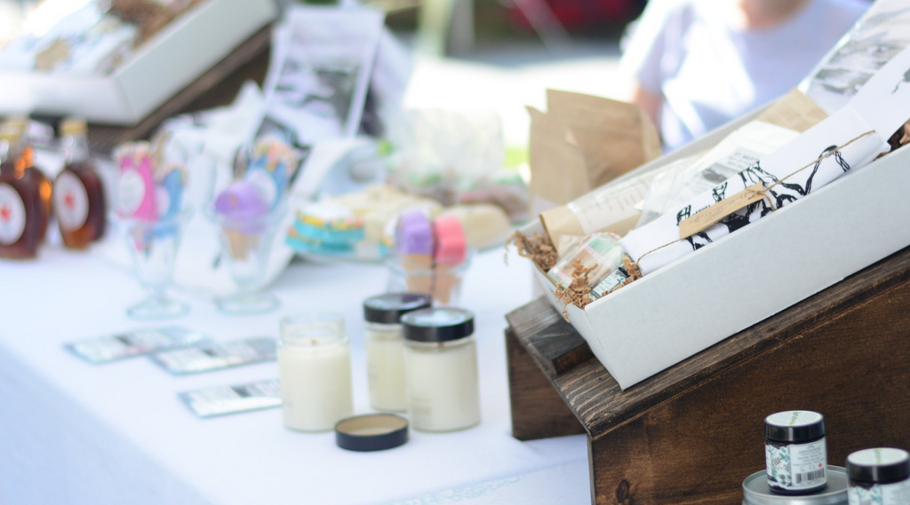 Products displayed on a table at a farmer's market. The table has a white cloth on it and there are candles and bath bombs in the frame.