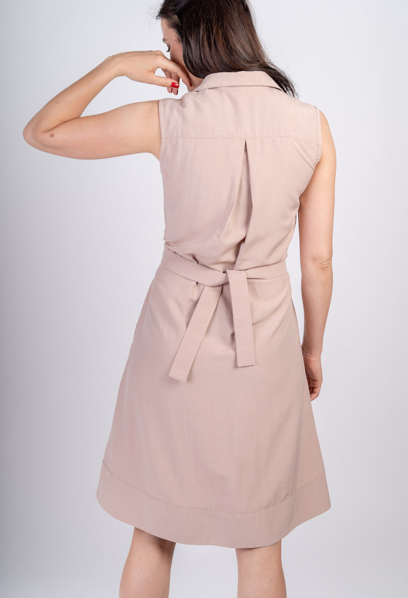 Backside of woman touching her face wearing Sonna knee length belted dusty rose beige dress by AYANI