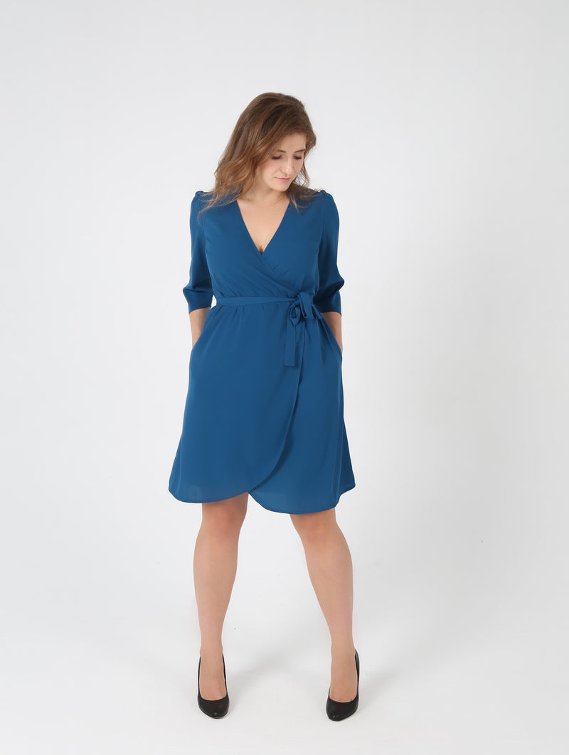 Woman looking down wearing belted collar royal blue dress by AYANI and black salon shoes