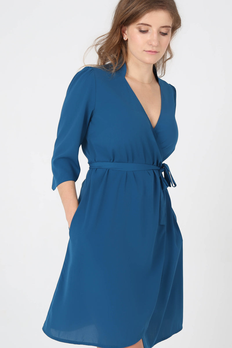 Woman looking down wearing belted collar royal blue dress by AYANI