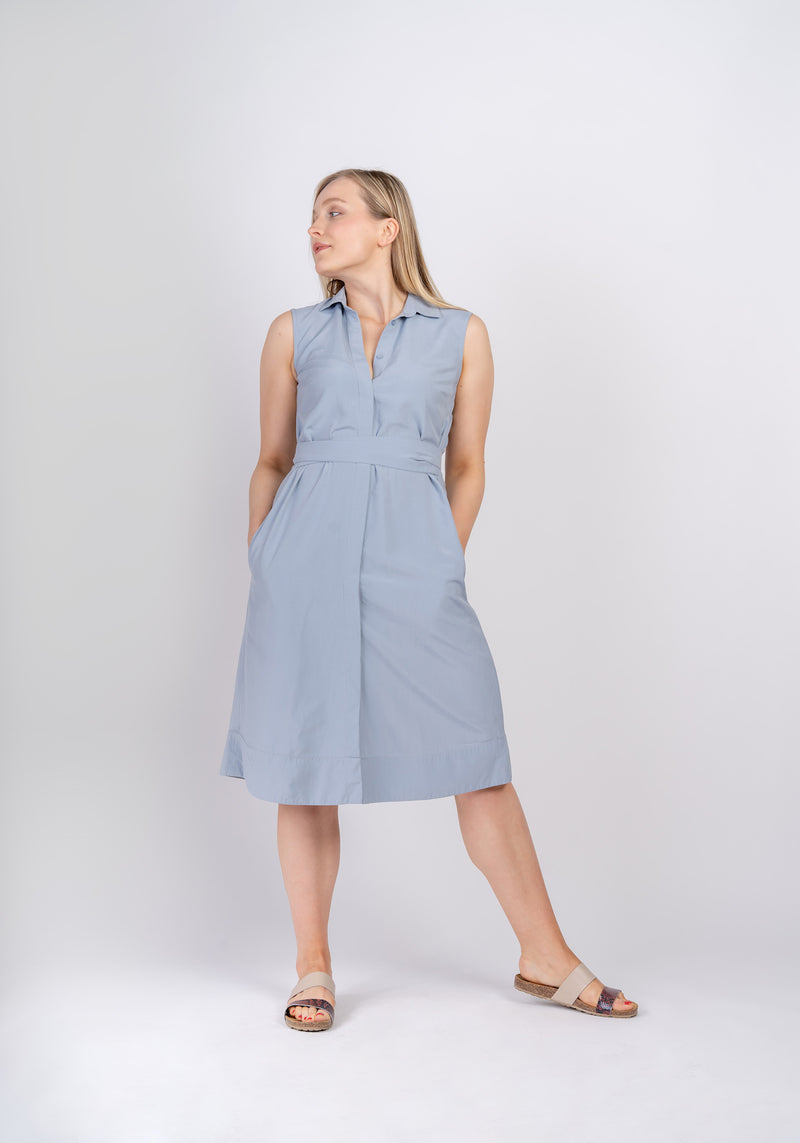 Woman looking to the side wearing Sonna belted powder light blue dress by AYANI and sandals