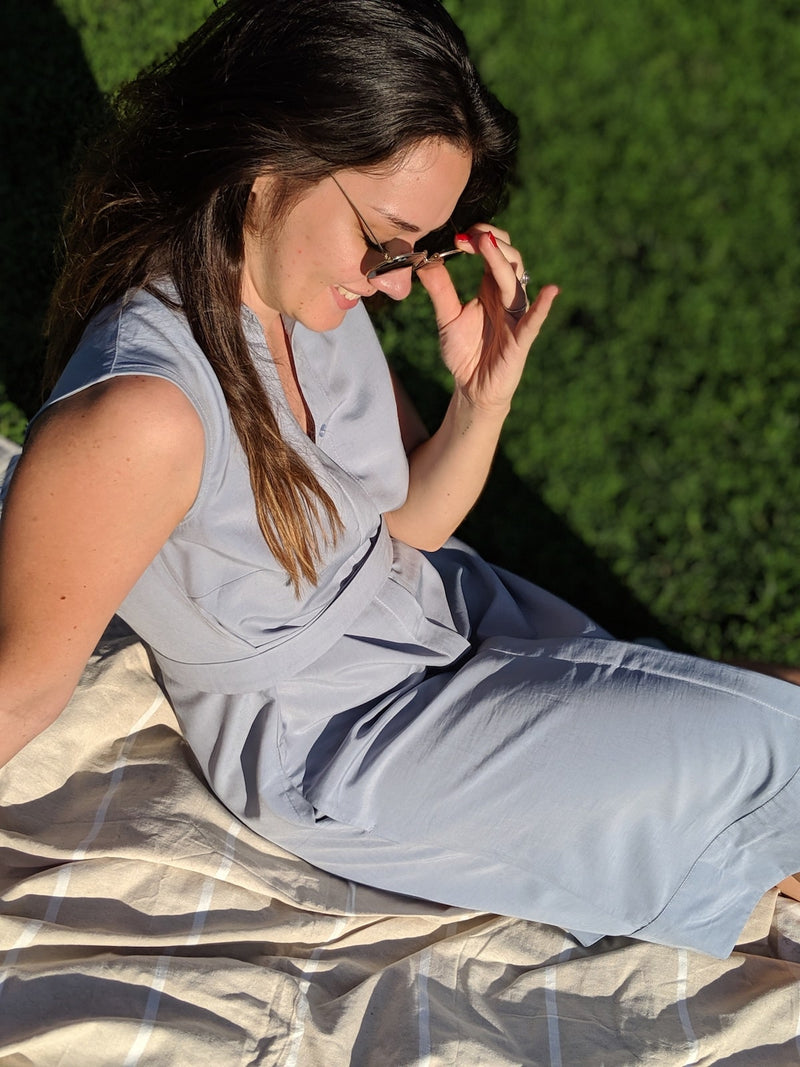 Woman sitting on a blanket on the grass wearing a Sonna belted powder light blue dress by AYANI