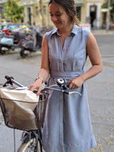 Woman smiling and holding a bike while wearing a Sonna powder light blue dress by AYANI