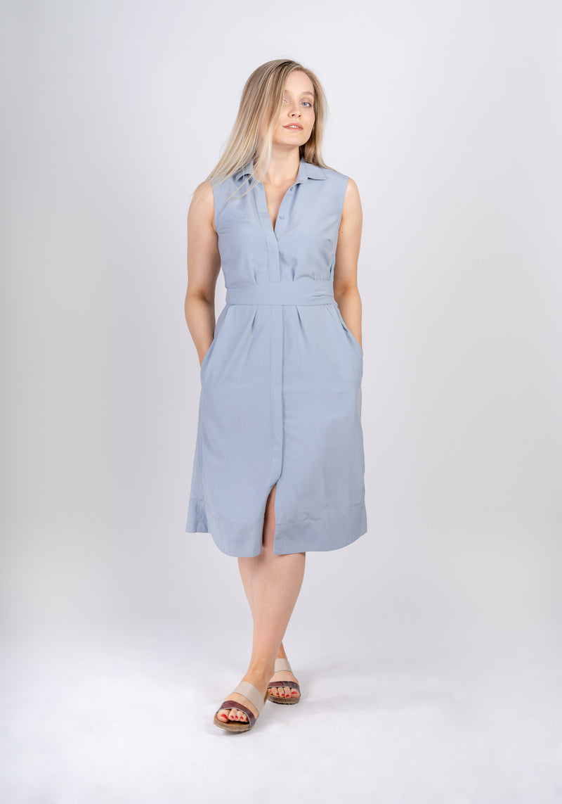 Woman standing with crossed legs and hands in pockets wearing Sonna belted powder light blue dress by AYANI and sandals