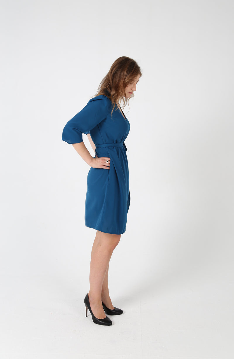 Woman turned on the side wearing wraped collar belted knee high royal blue dress by AYANI and black salon shoes