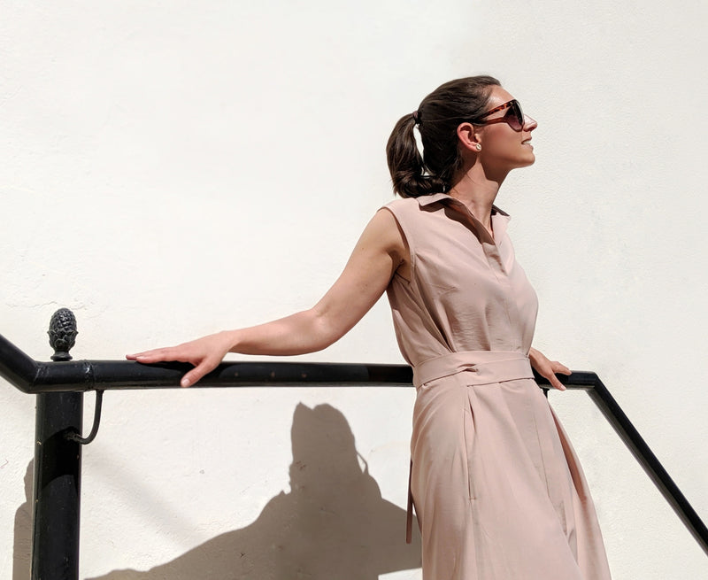 Woman turned on the side with arms on handrail wearing Sonna belted dusty rose beige dress by AYANI and sunglasses