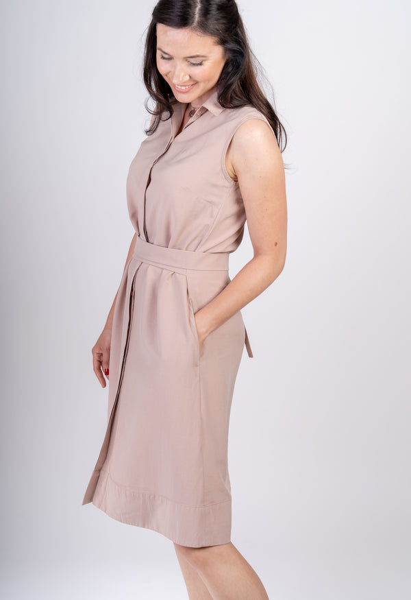 Woman turned on the side with hand in pocket wearing Sonna belted dusty rose beige dress by AYANI