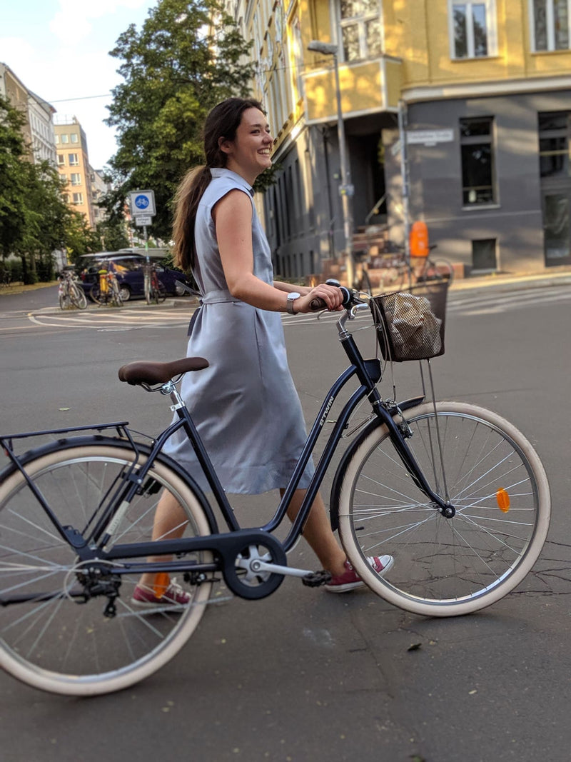 Woman walking on the street holding a bike and wearing a Sonna belted powder light blue dress by AYANI and converse