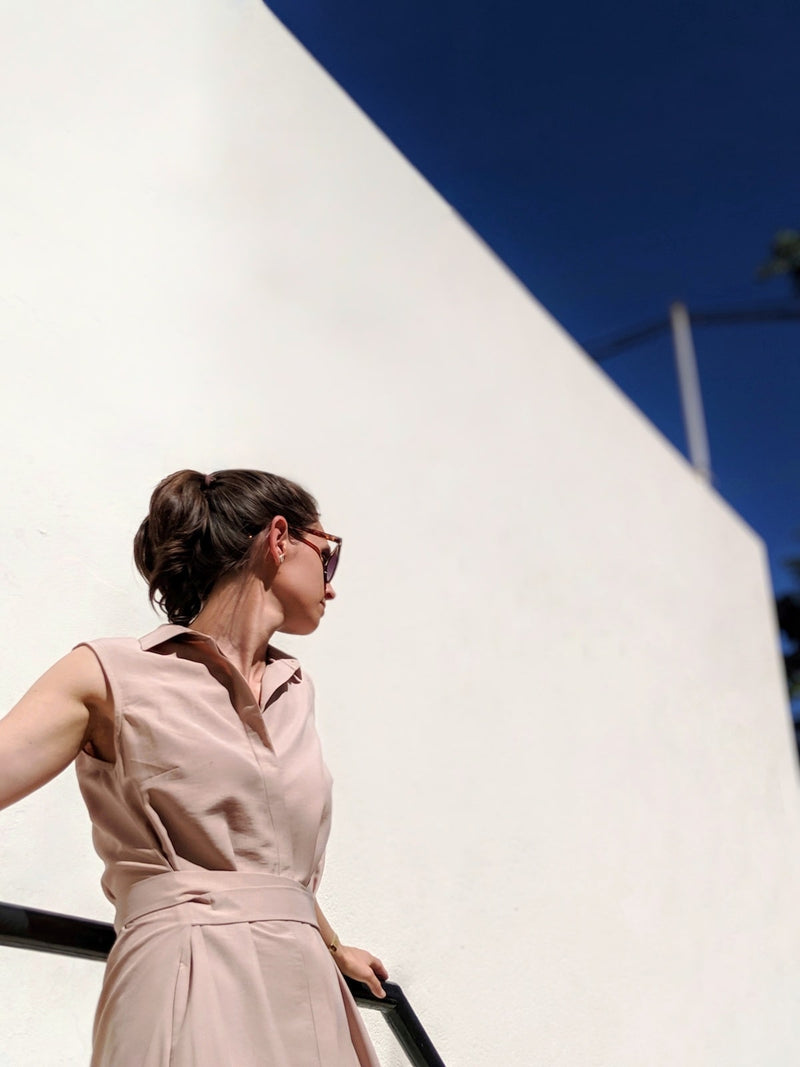 Zoom into upper torso of woman looking to the side wearing Sonna belted dusty rose beige dress by AYANI and sunglasses