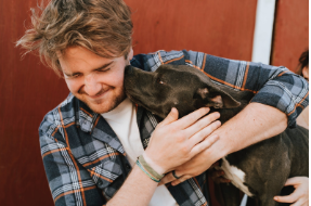 dog licking man on the face, smiling and laughing