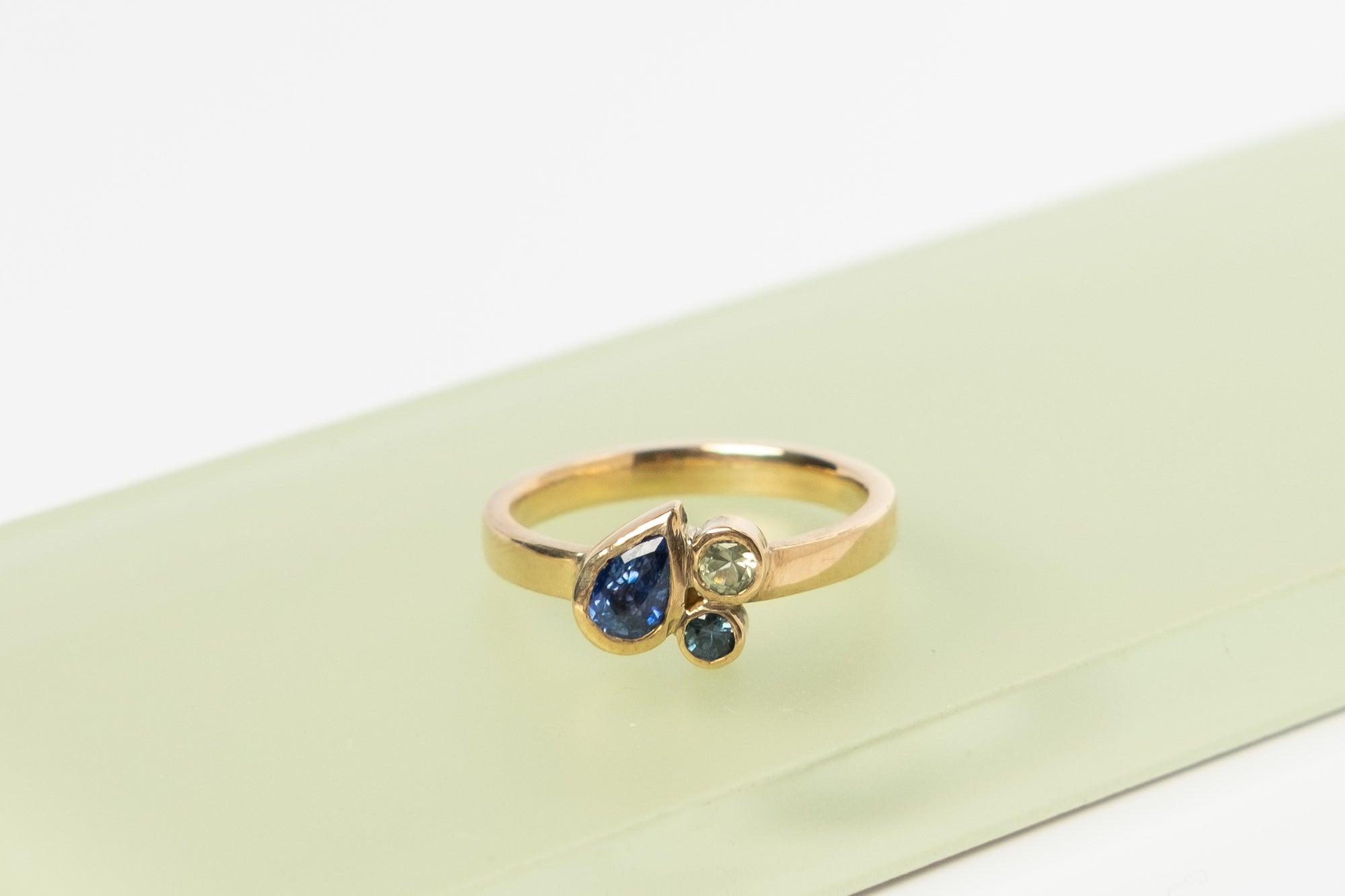 Gold ring with a cluster of bezel set sapphires including a blue pear cut and two smaller round sapphires - teal and green
