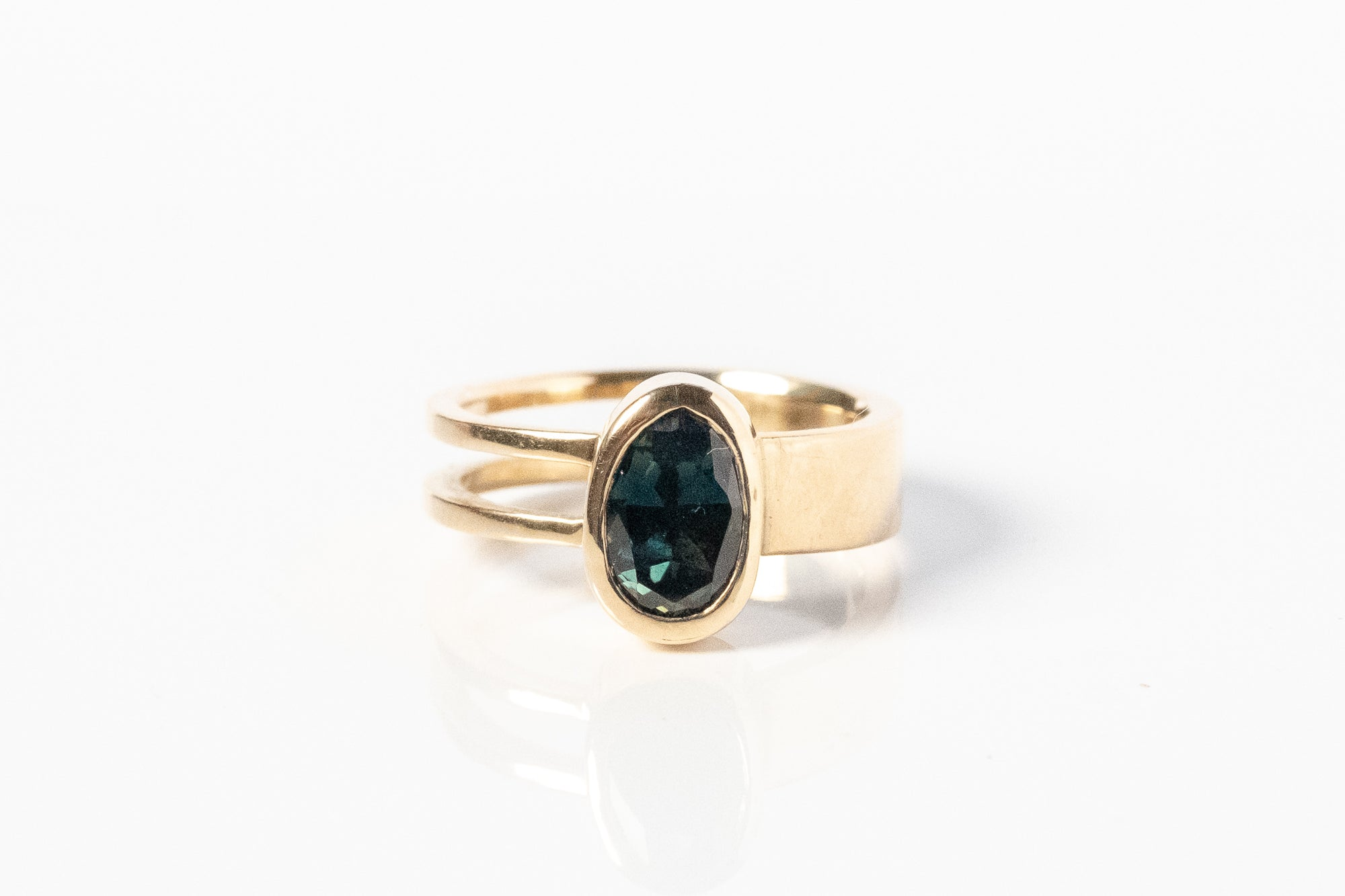 Gold ring with oval, bezel set, midnight blue sapphire