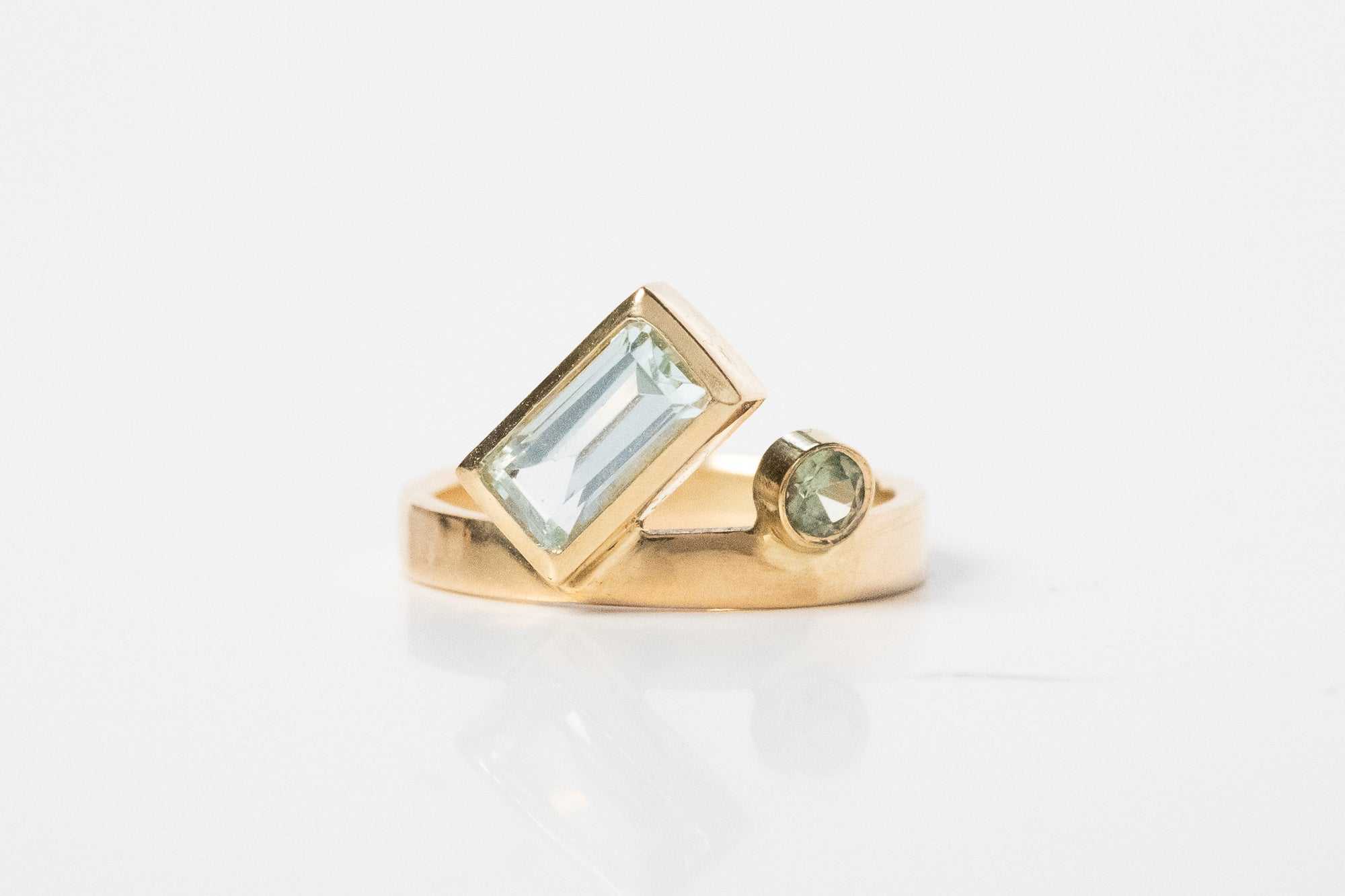 Gold ring with emerald cut, bezel set aquamarine, set at an angle and a small, round, green sapphire set atop the ring band
