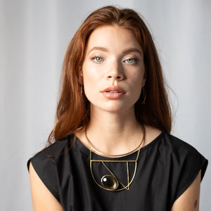 Woman wearing large, brass, statement collar necklace with geometric design and golden obsidian