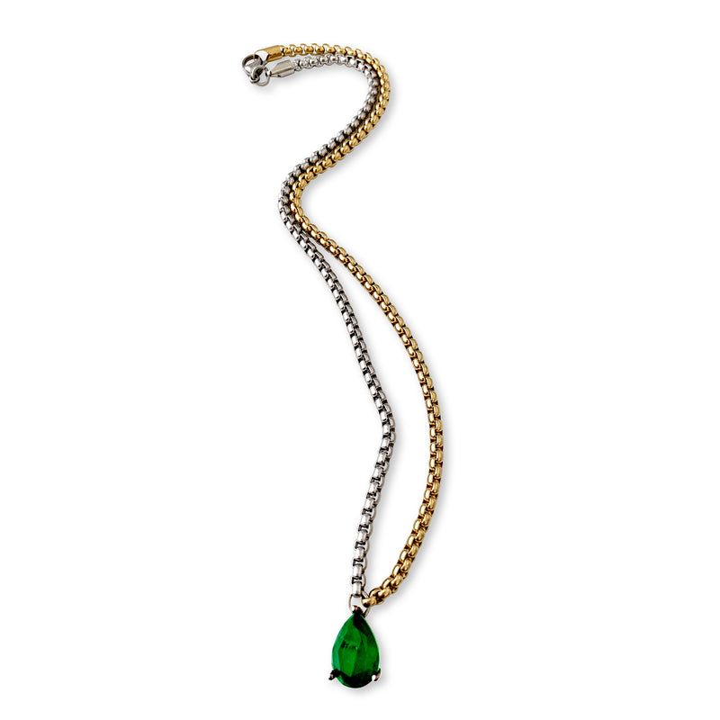 Drop necklace which is a half gold and half silver necklace with tear drop shaped pendant that has emerald stone on it.