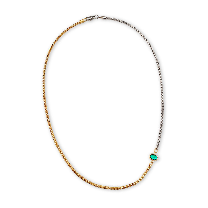 Emerald Point Necklace which is a half gold and half silver thin chain separated with a small green emerald stone.