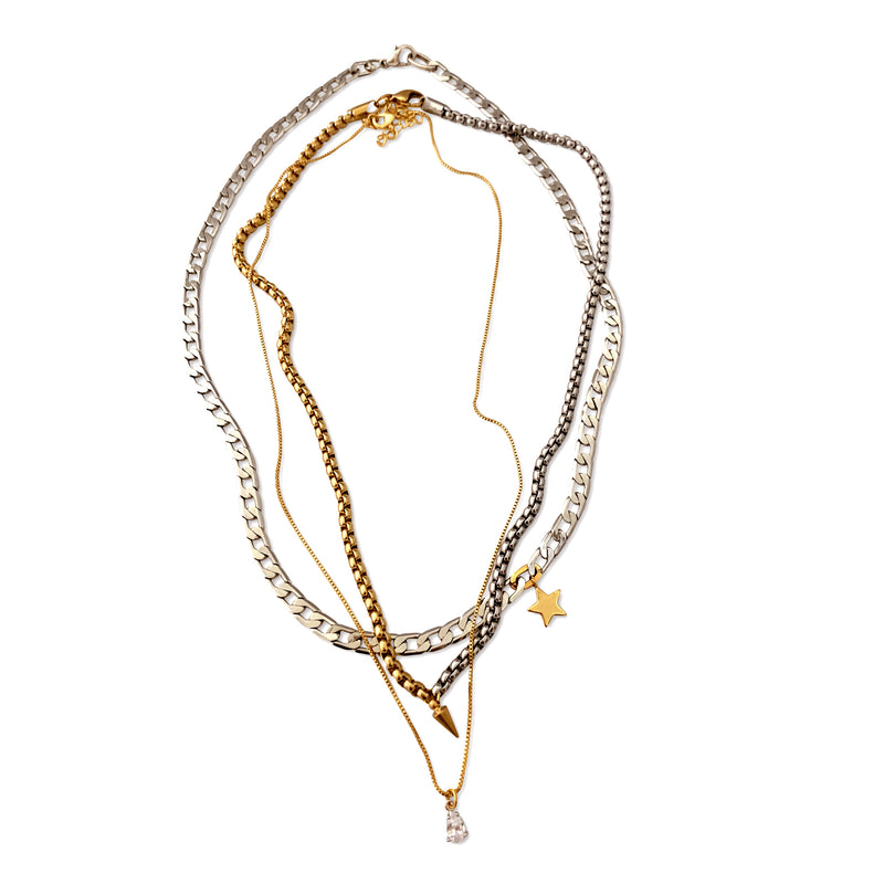 SHINI SPIKE TRIO SET which is a 3 Chains Layered Set which are 16inch - 17inch -18inch in length. One is a Thin Brass Gold Plated, Brass Link Chain and Rhodium plated, Stainless Steel Chains. The necklaces come with a Zirconia Drop Mini Pendant, Brass Gold Plated Spike and Star Pendant.