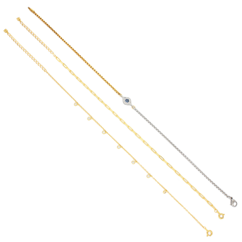 3 piece Dot Anklet set which comes with a gold thin chain with 7 small hanging crystal charms, gold chain and mix gold and silver chain separated with an eye shaped charm with stones in it.