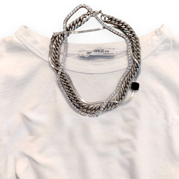 Tropicana chain, tennis necklace and silver snake chain with Black emerald details placed on top of a white T-shirt.