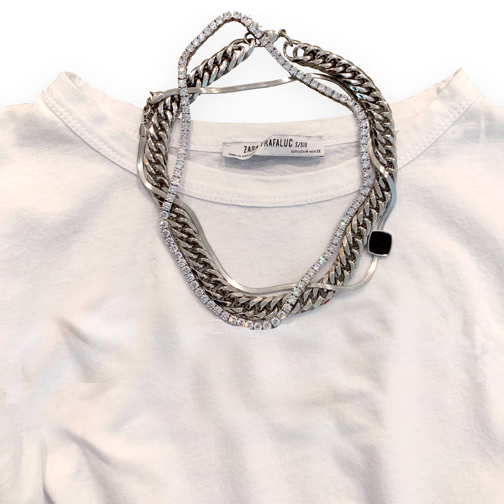 Synergy Set which comes with two necklaces. One is the palma necklace which is a silver chain with box type lock and another one is the tennis necklace made of Clear Zirconia Stones. It is layered with the Square snake in silver necklace placed on top of a white tshirt.