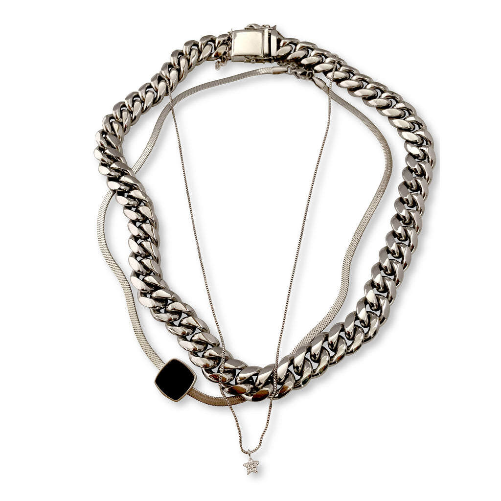 3 Chains Layered SNAKE SET  comes with  3 Silver Stainless Steal Chains. One has a Micro Pave Star Charm, next is a silver chain with black square enamel charm and the Palma Chain necklace in Silver.