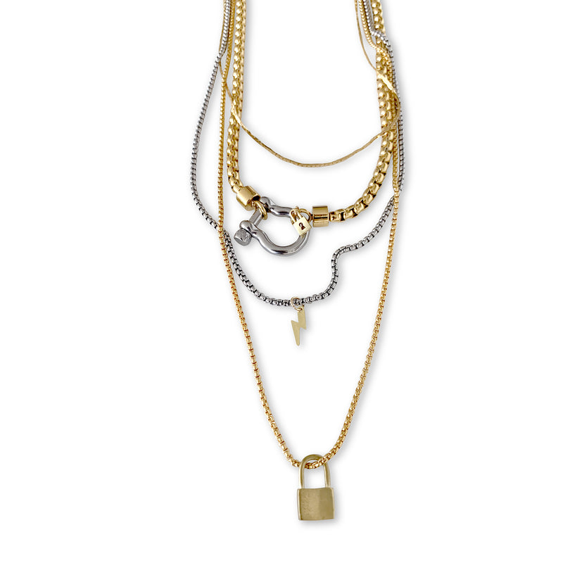 Herradura Lock which is 4 Chains layered set comes with a thin gold necklace, Herradura chain in gold with Silver clasp, longer silver chain with lightning bolt pendant and the longest is a gold necklace with keylock pendant in gold.