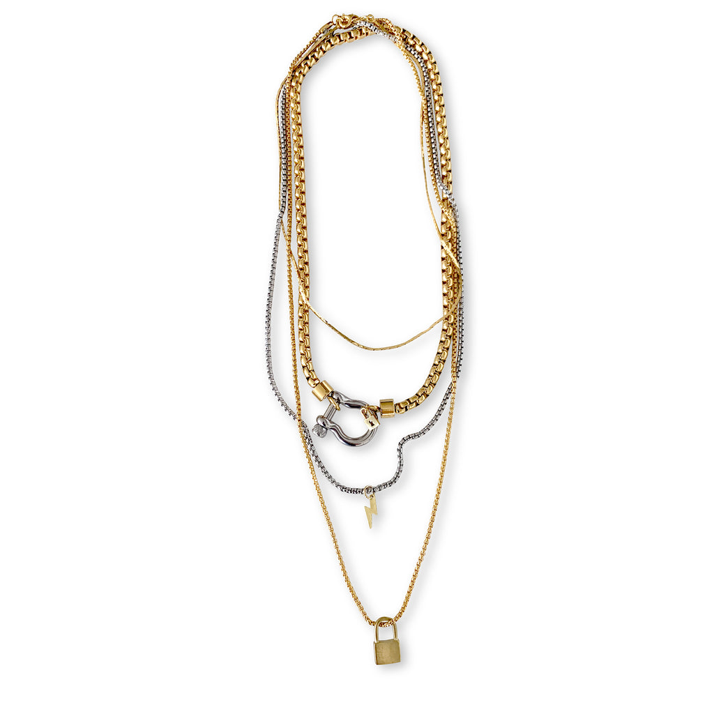 Herradura Lock which is 4 Chains layered set comes with a thin gold necklace, Herradura chain in gold with Silver clasp, longer silver chain with lightning bolt pendant and the longest is a gold necklace with a keylock pendant in gold.
