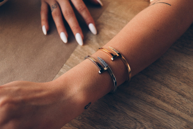 Model wearing two Clavo Shini bangles, comes in Gold and Silver color. The design is similar to a nail with sparkling stones in one end and flat surface on the other.