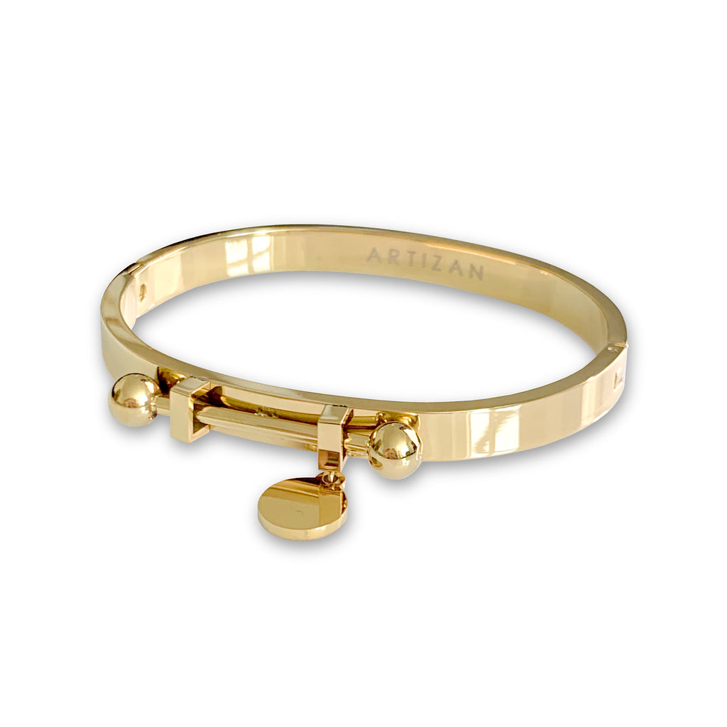 Coins bangle which is shiny gold with a bar in the center and a coin charm hanging on it.