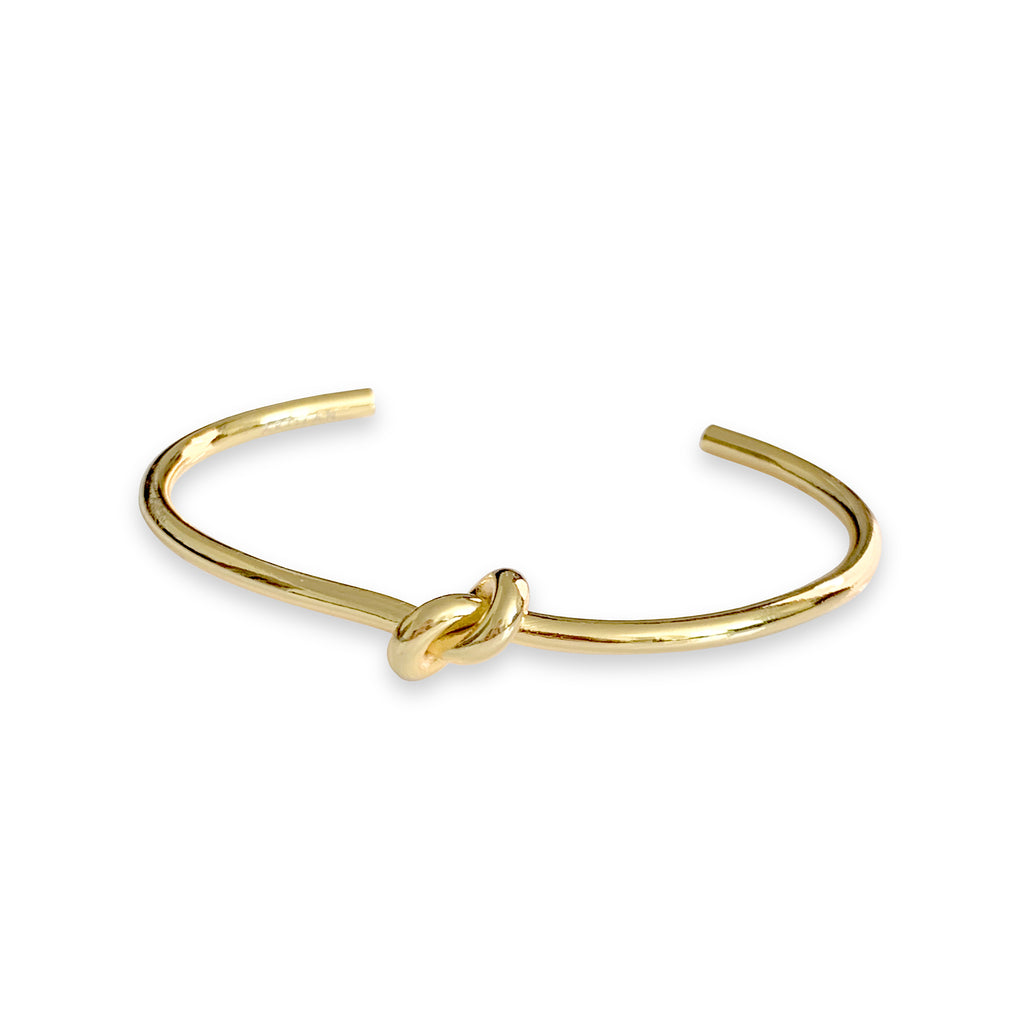 Knot bangle which is an open bracelet in gold with a knot design in the center.