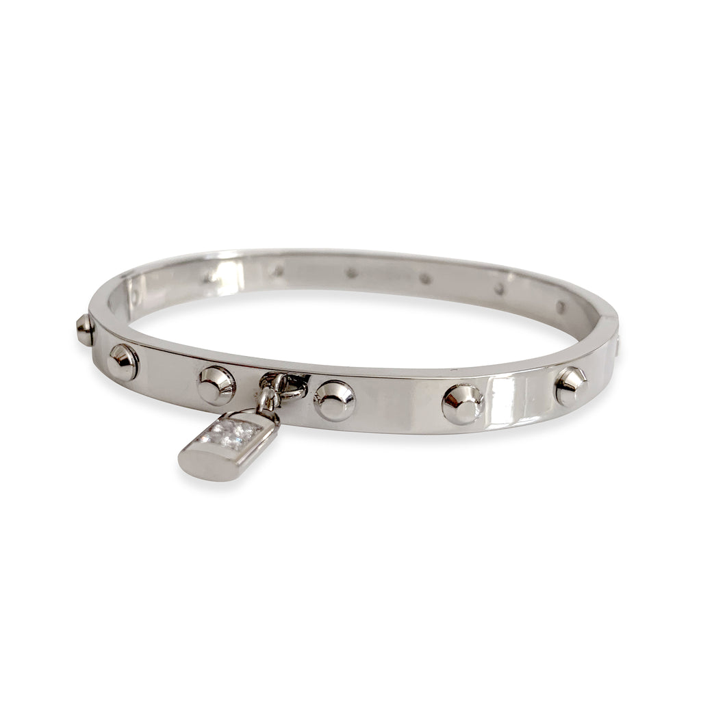 Lock bangle which is a silver bangle with a lock charm. it has few flat spikes around the bangle.