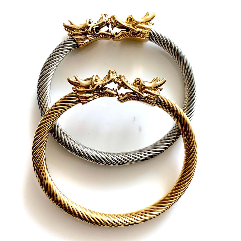 Two Dragon Bracelets in gold plated and rhodium plated stainless steel. it has two dragon heads facing each other.