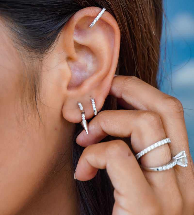 Model wearing the Clear Ear Cuff Silver on the upper part of her ear made of 925 Sterling silver with Cubic Zirconia around it and 2 small silver loop earring with spikes detail. She also wears a silver diamond ring and the wraparound ring.
