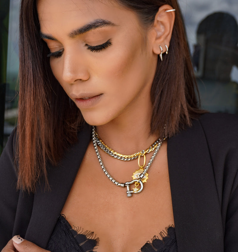 Model wearing 3 earrings that are part of the Ear Part Set, clear ear cuff and two small hoop earrings in Silver. She is also wearing the Herradura Necklace in silver and chain necklace with eye pendant in mix gold and silver.